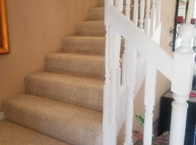 Angled White Handrail Accompanying A Carpeted Staircase