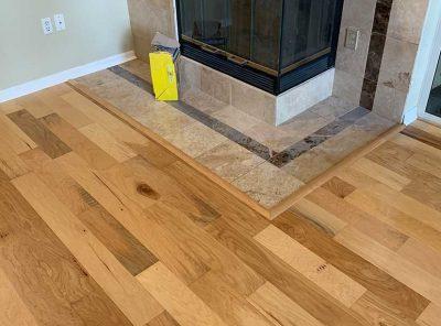 Hardwood Floor Surrounding A Tiled Fireplace