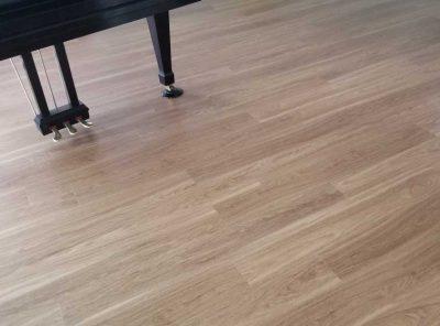 Light-Colored Vinyl Flooring Underneath A Grand Piano